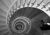 Photograph of a man descending a spiral staircase.