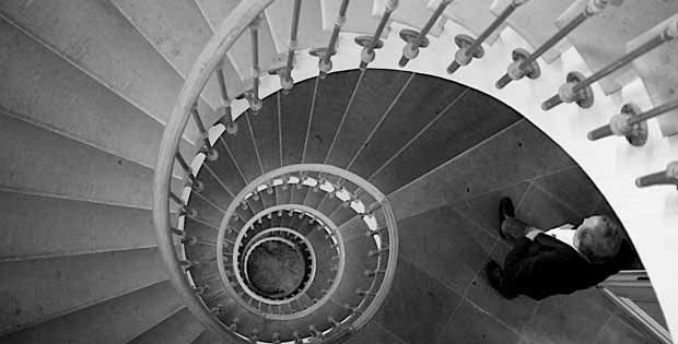 Photograph of a man descending a spiral staircase.