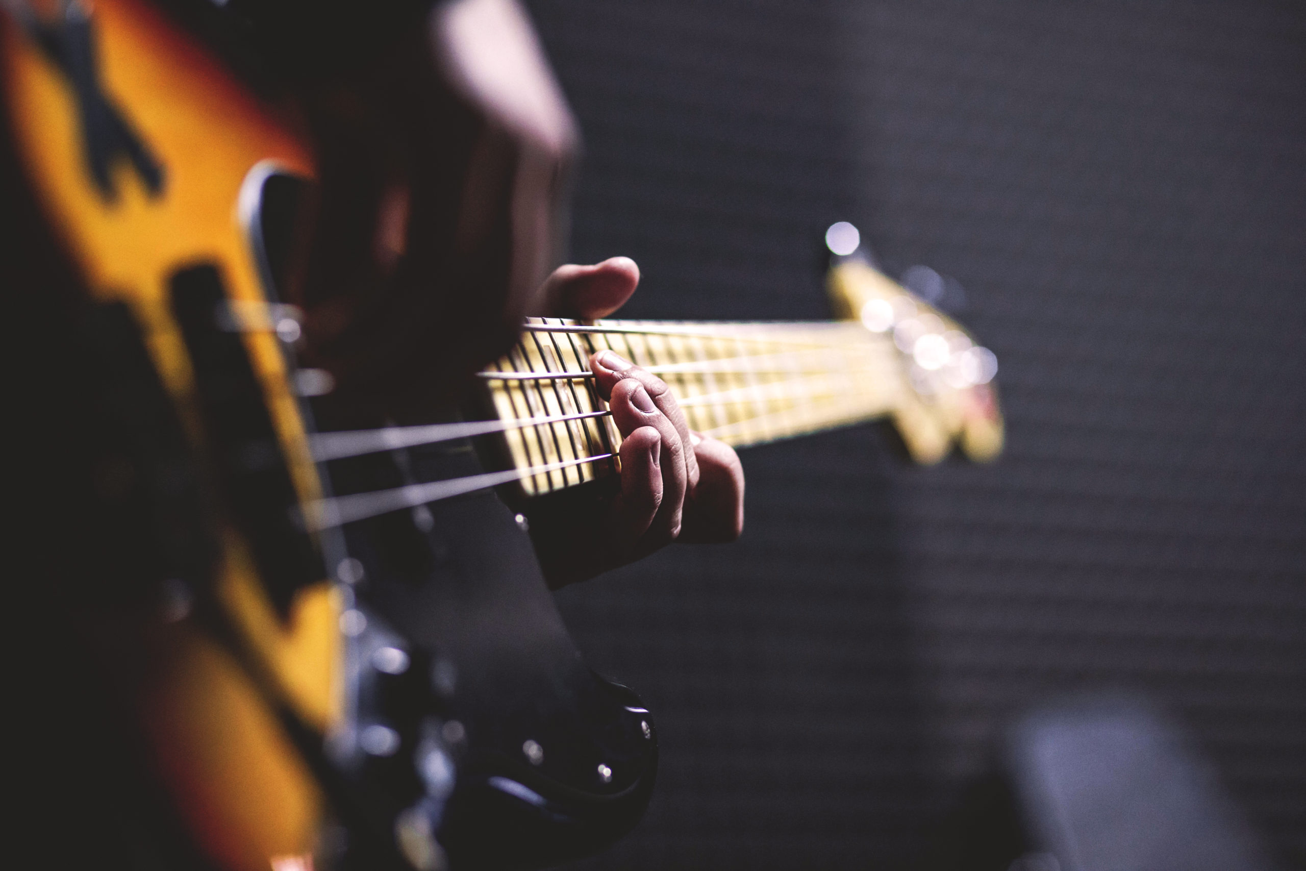 Photo of a musician playing sun burst electric bass guitar in bokeh photography.