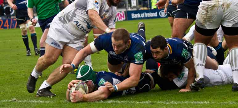 Rugby players dive for the ball. Image Credit: Tony McIntyre, via Flickr/CC.