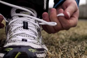 "Still image of runner lacing up shoes from ""Marathon Thoughts"" by Improv Asylum."