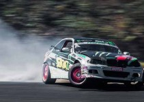 Photograph of a speeding rally car with a huge plume of smoke trailing behind it.
