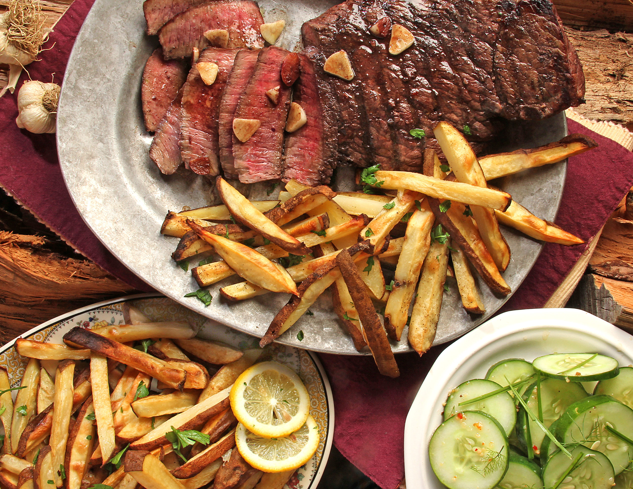 Photo of a steak and french fries on a glass plate.