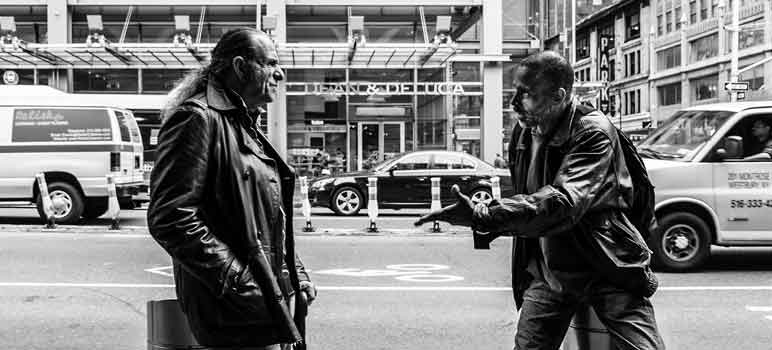 Two men stop to have a conversation on the street. Image Credit: Jim Pennucci, via Flickr/CC.