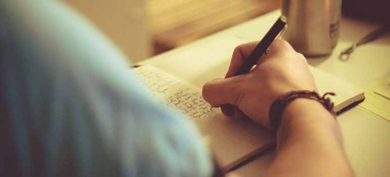 Photo of person writing in a notebook. Image Credit: Roco Julie, via Flickr/CC.